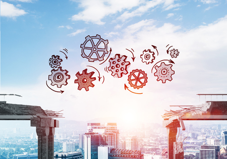 Sketched gear mechanism over gap in concrete bridge as symbol of teamwork and problem solving. Cityscape and sunlight on background. 3D rendering. Stock Photo
