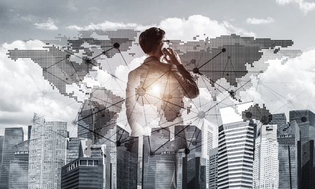 Double exposure of elegant businessman standing with back and talking his mobile phone