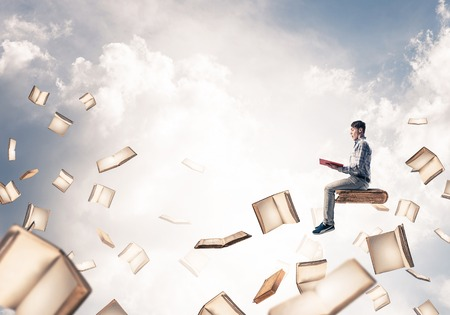 Young shocked man floating in blue sky with red book in hands Stock Photo