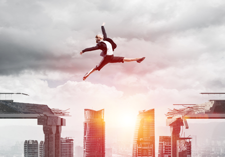 dangerous ideas: Business woman jumping over gap in concrete bridge as symbol of overcoming challenges. Sunlight and cityscape on background. 3D rendering. Stock Photo