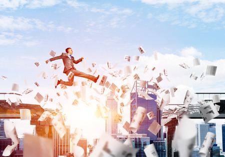 dangerous ideas: Businessman jumping over gap with flying paper documents in concrete bridge as symbol of overcoming challenges. Cloudly with sunlight skyscape on background. 3D rendering.
