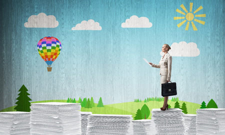 Confident business woman in suit standing on pile of documents with sketched landscape view on background. Mixed media. Stock Photo