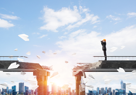 Engineer in suit and helmet looking in binoculars while standing among flying paper planes on broken bridge with cityscape and sunlight on background. 3D rendering.