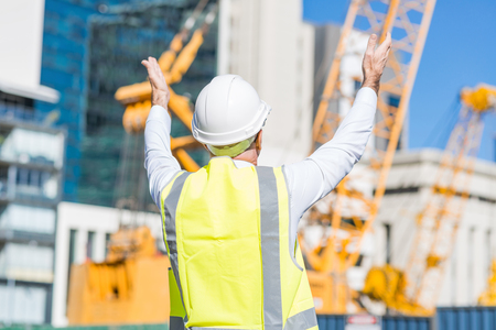 master: Engineer man in helmet and jacket controlling outdoor construction site