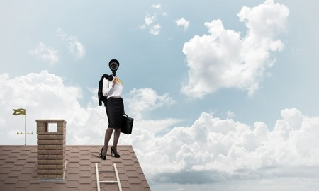 Faceless businesswoman with camera zoom instead of head standing on house roof photo