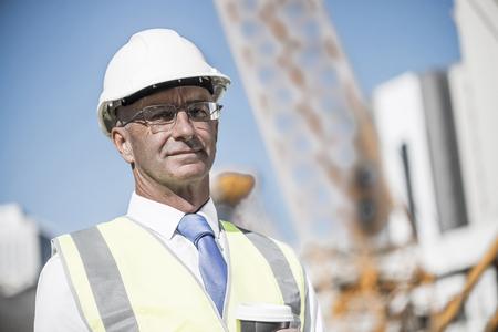 master: Senior engineer man in suit and helmet outdoor having coffee