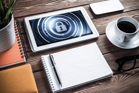 table top: Business workplace with office stuff and tablet with padlock icons on screen