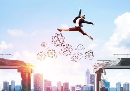 Bedrijfsvrouw springen over kloof met versnellingsmechanisme in betonnen brug als symbool om uitdagingen te overwinnen. Cityscape en zonlicht op de achtergrond. 3D-weergave. Stockfoto