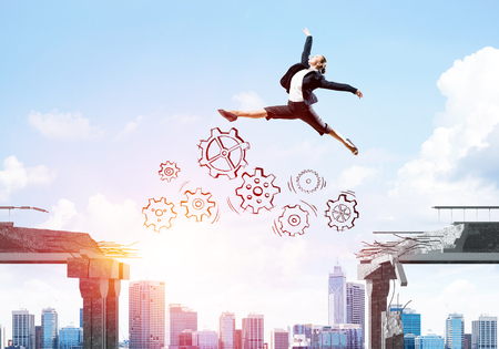 Business woman jumping over gap with gear mechanism in concrete bridge as symbol of overcoming challenges. Cityscape and sunlight on background. 3D rendering. Stock Photo