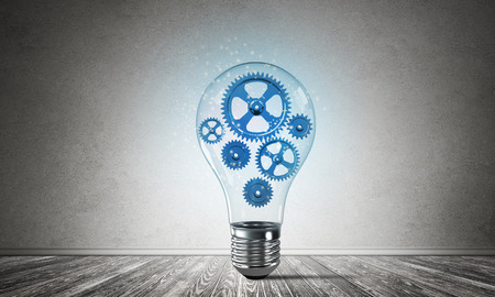 Glass lightbulb with multiple blue gears inside placed in empty room with grey wall on background. 3D rendering.