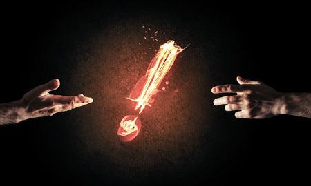 Handen bereiken elkaar en brandend gloeiend uitroepteken Stockfoto