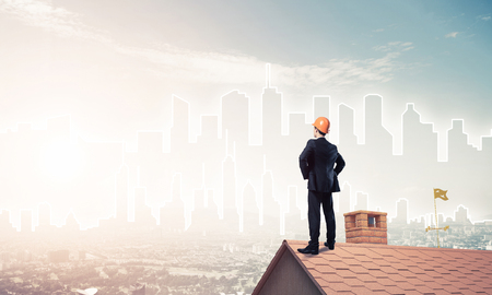 Young businessman in suit and helmet on roof edge. Mixed media photo