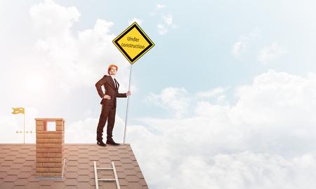 Man holding safety sign indicating under construction notice. Mixed media photo