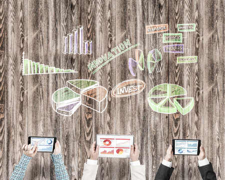 table top: Group of three people with devices in hands working together as symbol of networking and communication
