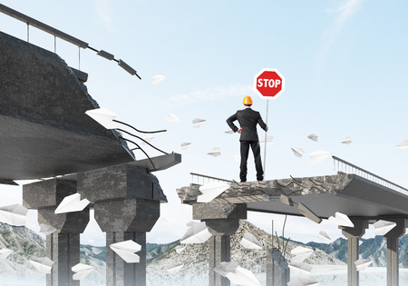 business obstacle: Rear view of engineer in helmet holding stop sign while standing among flying paper planes on broken bridge with skyscape on background. 3D rendering.