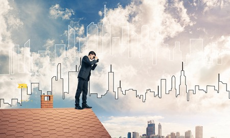Young businessman viewing cityscape in his binoculars Mixed media Stock Photo