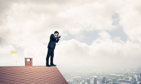 Young determined businessman standing on house roof and looking in binoculars. Mixed media