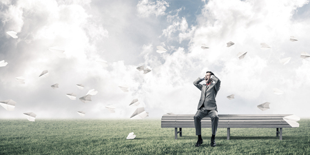 noise isolation: Frustrated businessman sitting on bench and closing ears with hands and paper planes fly around