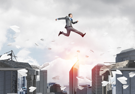 Businessman jumping over gap with flying paper planes in concrete bridge as symbol of overcoming challenges. Cityscape with sunlight on background. 3D rendering. Stock Photo