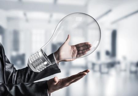 Closeup shot of business woman hands holding light bulb Stock Photo