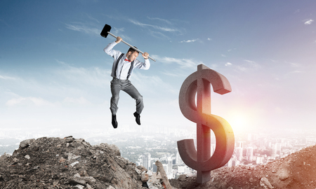 Jumping businessman crashing big dollar symbol with city view and sunlight on background.