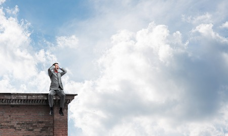 noise isolation: Frustrated businessman sitting on building top and closing ears with hands