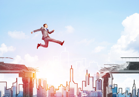 Businessman jumping over gap in concrete bridge as symbol of overcoming challenges. Sunlight and cityscape on background. 3D rendering.