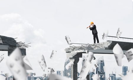 Young engineer in suit and helmet looking in spyglass while standing among flying papers on broken bridge with cityscape on background. 3D rendering.
