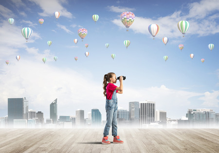 careless: Cute kid girl standing on wooden floor and aerostats flying in air