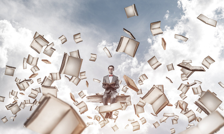 Funny man in red glasses and suit sitting on book and reading