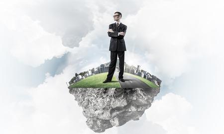 푸른 하늘에 녹색 떠있는 섬에 서있는 우아한 자신감 사업가 스톡 콘텐츠