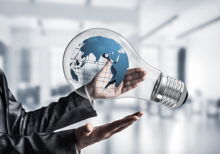 Closeup of business woman in suit holding in hands lightbulb with Earth globe inside with office view background.