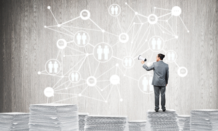 Businessman with speaker in hand standing on pile of documents with social network structure on background. Mixed media.