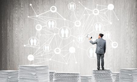 Homme d'affaires avec haut-parleur à la main, debout sur une pile de documents avec la structure de réseau social sur le fond. Technique mixte. Banque d'images - 84795791