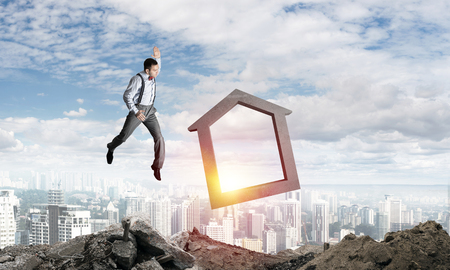 Jumping businessman crashing big house symbol with city view on background. 3D rendering. Stock Photo