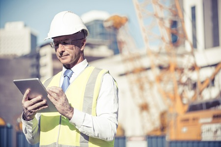 Senior engineer man in suit and helmet working on tablet pc Stock fotó