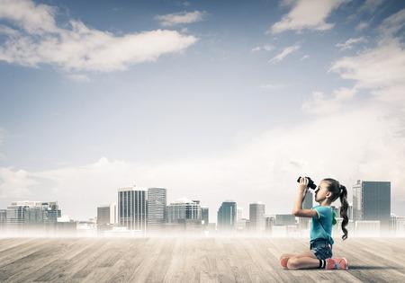careless: Cute kid girl sitting on wooden floor and looking in binoculars