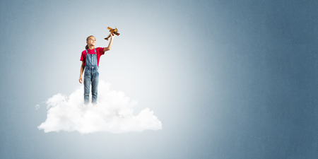 Cute kid girl standing on cloud and playing with airplane toy Reklamní fotografie