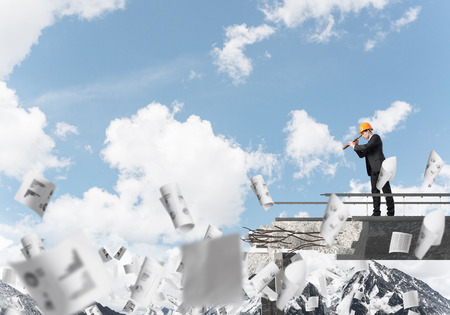 Young engineer in suit and helmet looking in spyglass while standing among flying papers on broken bridge with skyscape on background. 3D rendering.