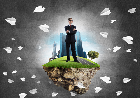 construction project: Elegant confident businessman standing on green floating island against concrete background