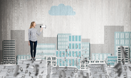 Woman in casual clothing standing among flying letters with speaker in hand with sketched cityscape view on background. Mixed media. Stock Photo