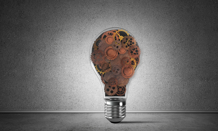rusty background: Glass lightbulb with multiple gears inside placed in empty room with grey wall on background. 3D rendering.