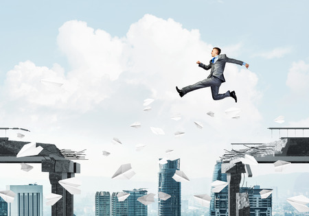 dangerous ideas: Businessman jumping over gap with flying paper planes in concrete bridge as symbol of overcoming challenges. Cityscape on background. 3D rendering. Stock Photo