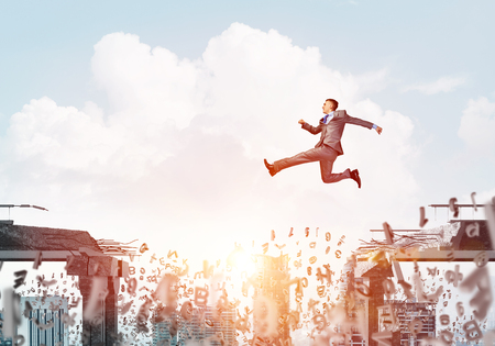 dangerous ideas: Businessman jumping over gap with flying letters in concrete bridge as symbol of overcoming challenges. Cityscape with sunlight on background. 3D rendering.