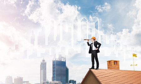 construction project: Young businessman in suit and helmet on roof edge. Mixed media Stock Photo