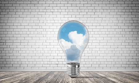 Glass lightbulb with clouds inside in empty room with grey brick wall on background. 3D rendering.