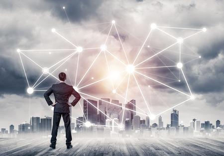 後ろに立って、ネットワーク描かれたコンセプトを見ているビジネスマン
