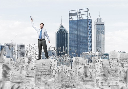 Young businessman keeping hand with book up while standing among flying letters with cityscape on background. Mixed media. Stock Photo