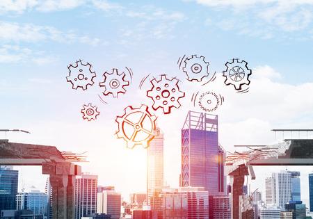 チームワークと問題解決のシンボルとして、コンクリート橋の隙間の上にスケッチギア機構。背景に都市の景観と日光。3D レンダリング。