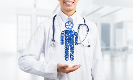doctor holding gift: Close of female hands holding person gear figure in palm Stock Photo
